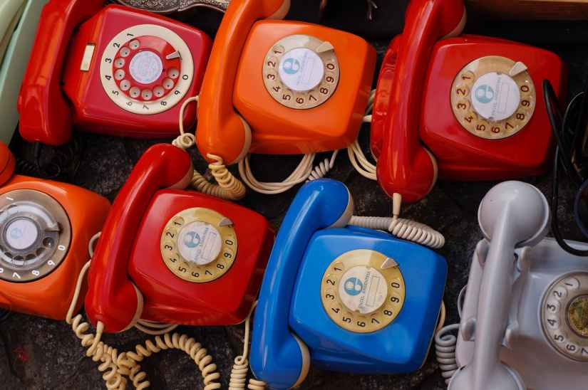 seven assorted colored rotary telephones