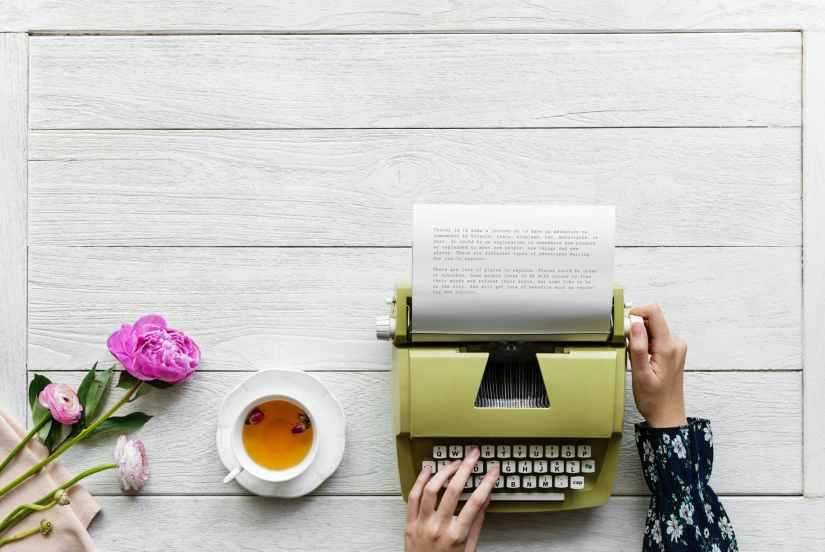 person using green typewriter